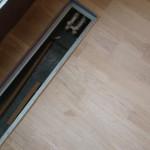 Grzejnik podłogowy, korek, a wokół parkiet dębowy.